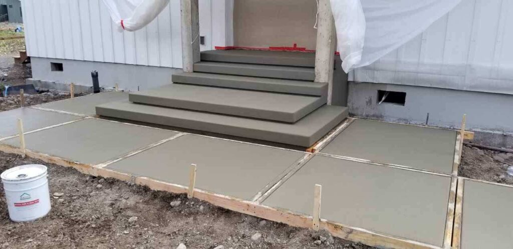 Poured concrete patio and steps in front of a door