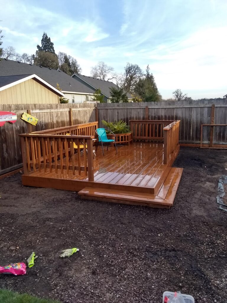 Small fenced, wooden deck decorated with chairs and plants in a dirt backyard
